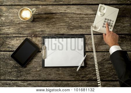 Top View Of Businessperson Making A Phone Call With His Office Telephone