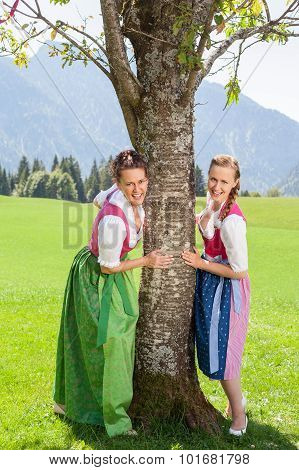 Two Smiling Women In Dirndl Hold On To A Tree.