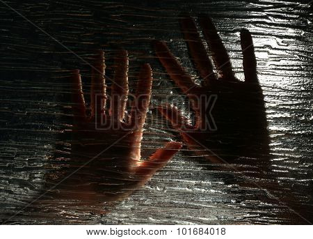 Female hand behind frosted glass, close-up