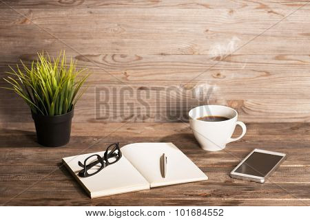 Working table with notepad, coffee cup , pen , smartphone , glasses, plant pot. Wooden table background with copy space on top. Soft focus with noise. Instant photo vintage split toning color effect.