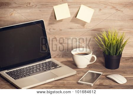 Wooden working desk with laptop, cup of hot coffee, mouse, smartphone and pot plant. Soft focus with noise in vintage toned.