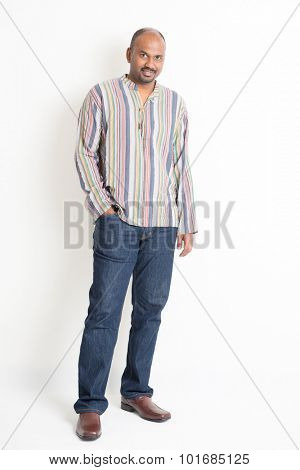 Full length confident mature Indian man in casual wear standing on plain background with shadow.