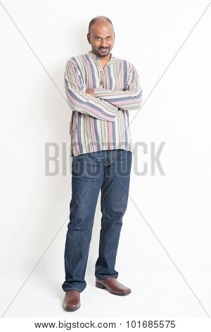 Full body confident mature Indian man in casual wear standing on plain background with shadow.