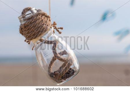 Glass jar of beautiful shells on sea background