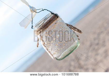 Glass lantern decorated with white lace hanging on wedding archway. Sea background