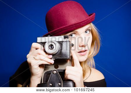 Young sensual lady in red hat with retro camera