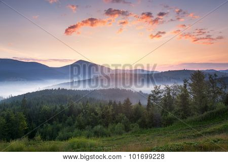 Stunning sunrise mountain landscape with vibrant colors and beautiful fog and clouds formations, summer time