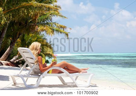 tropical woman on lounge with a coconut cocktail