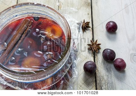 Homemade Pickled Plums  In A Glass Jar On Rustic Wood