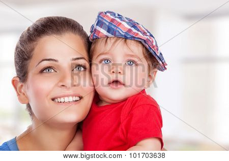 Portrait of happy young mother with cute little son at home, with pleasure spending time together, enjoying motherhood