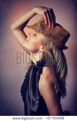 Side view of beautiful woman dancing in night club, closing eyes of pleasure, wearing stylish shiny hat, celebrating new year holiday