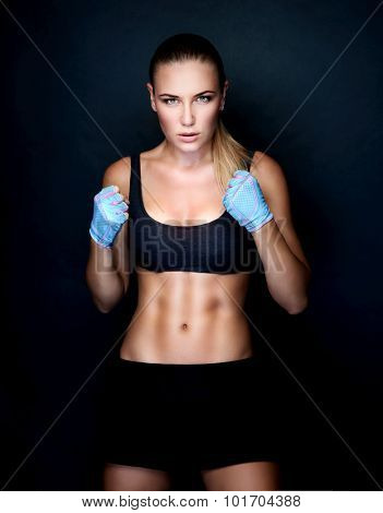 Beautiful boxer girl wearing sportive clothing and gloves practicing in the studio over black background, perfect athletic body, healthy lifestyle