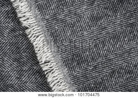 Herringbone wool tweed fabric background with closeup on textile texture and overlapping fringe edge