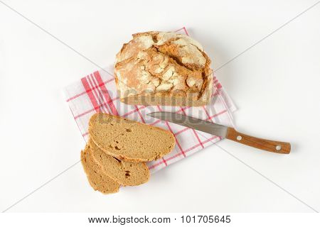 sliced loaf of bread and kitchen knife on checkered dishtowel