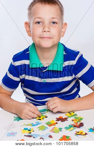 Cute little boy playing puzzles at the table