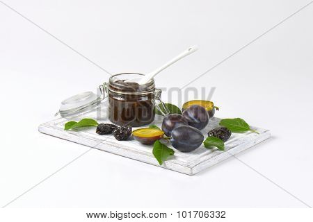 plum jam, fresh and dried plums on wooden cutting board