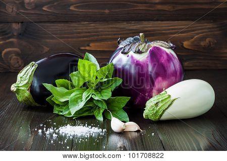 Purple and white eggplant (aubergine) with basil and garlic on dark wooden table. Fresh raw farm veg