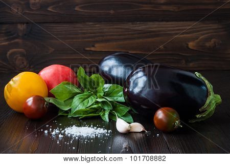 Eggplant (aubergine) with basil garlic and tomatoes on dark wooden table. Fresh raw farm vegetables