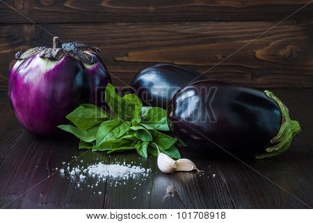 Eggplant (aubergine) with basil and garlic on dark wooden table. Fresh raw farm vegetables - harvest