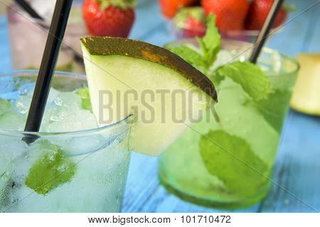 closeup of a glass with an appetizing melon mojito on a rustic blue wooden table with other different mojitos