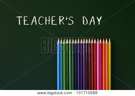 some coloured pencils of different colors and the text teachers day written in a green chalkboard
