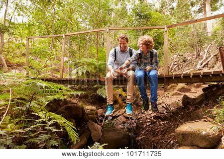 Father and son sitting on a bridge in a forest playing