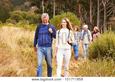 Multi-generation family walking together through a forest