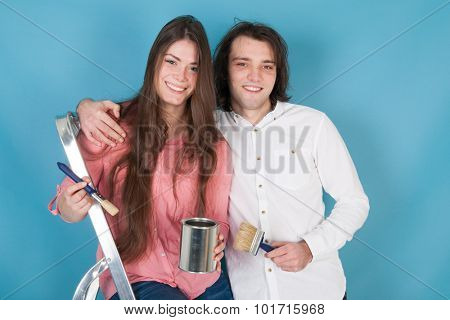 Young couple with paint and brushes in interior