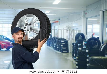Smiling repairman with tire a in car repair service.