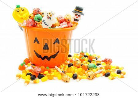 Halloween Jack-o-lantern candy pail with pile of candy