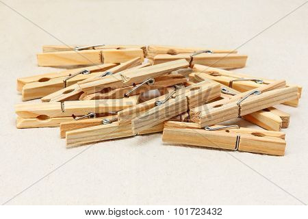 Wooden Clothespins On White Fabric Background.