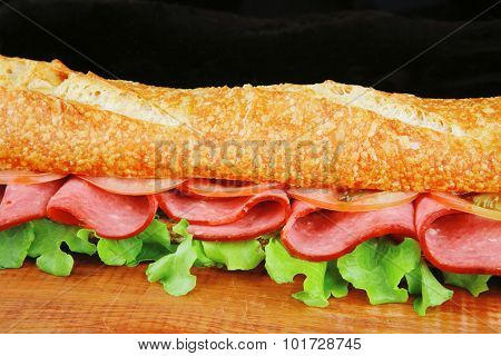 french long baguette with smoked chicken sausage on wood over black