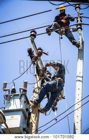 Electricians Working On Electricity Pole