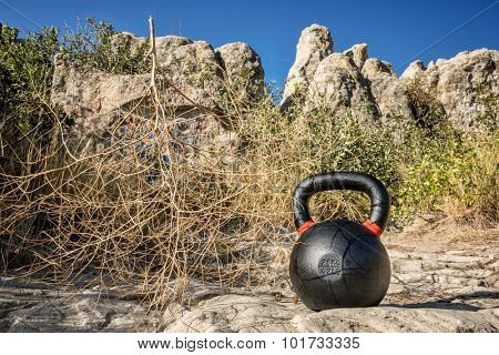 outdoor fitness concept - heavy iron kettlebell at rock outcropping with a tumbleweed
