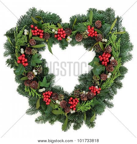 Christmas heart shaped wreath with holly mistletoe, ivy, pine cones and winter greenery over white background.