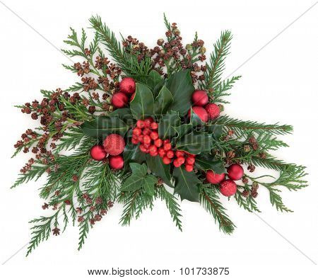 Christmas and winter flora with red bauble decorations, holly, ivy, fir and cedar cypress over white background.