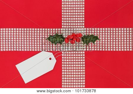 Christmas gift wrapping with diamond bling ribbon, tag and holly over red background.