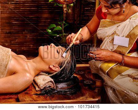 Woman having facial mask at ayurveda spa.