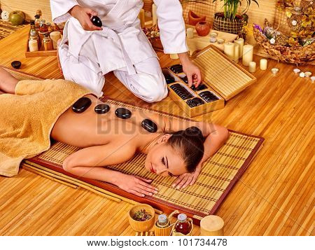 Woman getting stone therapy in bamboo spa. Male massage therapist.