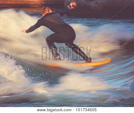 motion blur of a surfer riding a wave in a full wet suit toned with a retro vintage instagram filter app or action effect (SHALLOW DOF action shot)