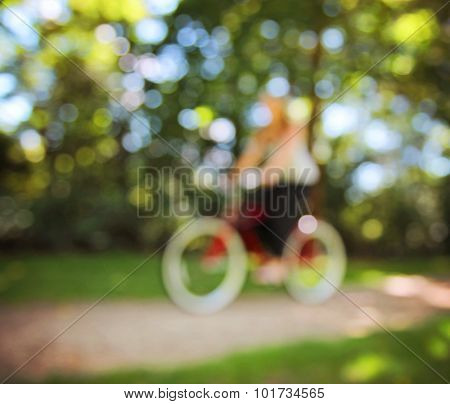 blurred image of a girl riding a bike on a path in a park full of trees toned with a retro vintage instagram filter