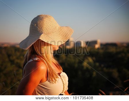 a pretty woman showing her profile at sunrise or sunset over a city landscape