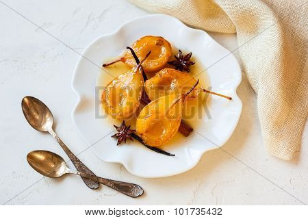 Poached pears with spices in syrup on the white plate. Delicious dessert for holiday