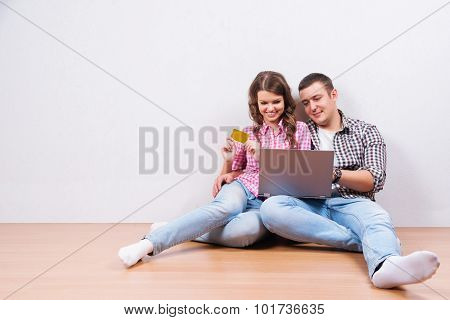 Shopping online together. Beautiful young loving couple shopping online while sitting on the floor
