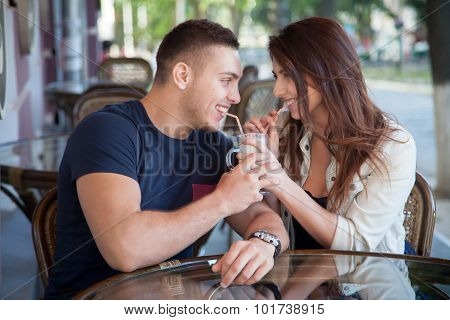 Young Man And Woman Sharing Drink In A Cafe