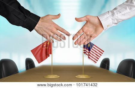 China and Malaysia diplomats agreeing on a deal