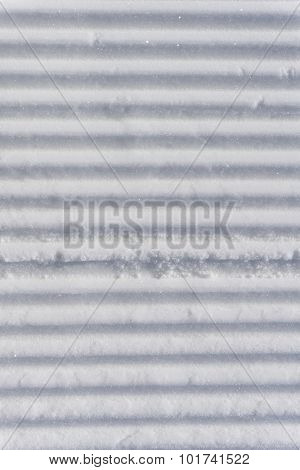 Fresh snow groomer tracks on a mountain ski piste, background