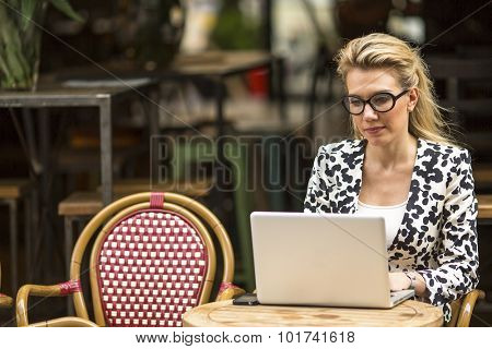 Young business woman with laptop in the cafeteria.