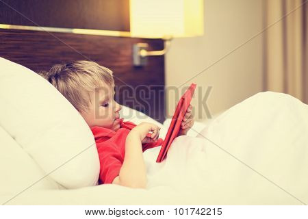 little boy looking at touch pad lying in bed of hotel room