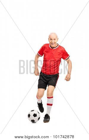 Full length portrait of a senior man in a red jersey playing football and looking at the camera isolated on white background